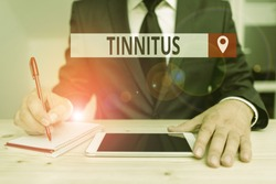 Writing note showing Tinnitus. Business photo showcasing A ringing or music and similar sensation of sound in ears.