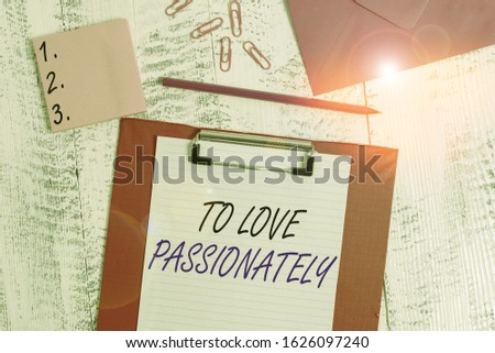 Writing note showing To Love Passionately. Business photo showcasing Strong feeling for someone or something else Affection Clipboard paper sheet pencil envelope clips notepad wooden background.
