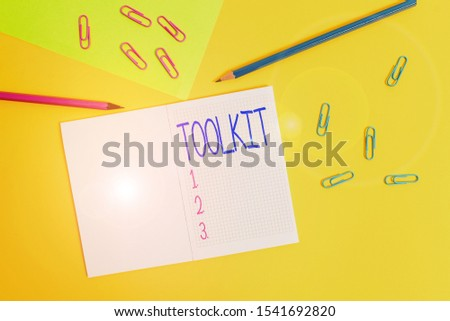 Writing note showing Toolkit. Business photo showcasing set of tools kept in a bag or box and used for a particular purpose Blank squared notebook pencils markers paper sheet colored background. #1541692820
