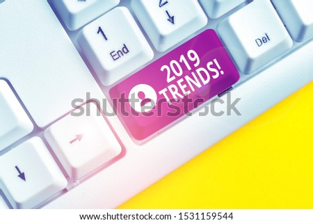 Writing note showing 2019 Trends. Business photo showcasing general direction in which something is developing or changing White pc keyboard with note paper above the white background.