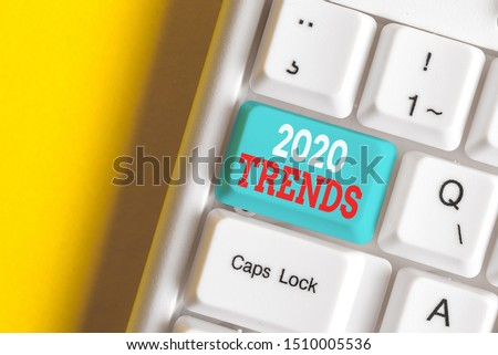 Writing note showing 2020 Trends. Business photo showcasing things that is famous for short period of time in current year White pc keyboard with note paper above the white background.
