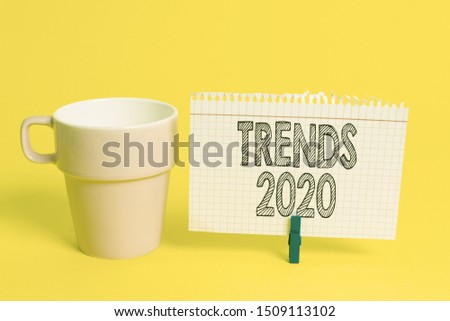 Writing note showing Trends 2020. Business photo showcasing Upcoming year prevailing tendency Widely Discussed Online Cup empty paper blue clothespin rectangle shaped reminder yellow office.
