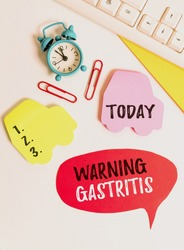 Writing note showing Warning Gastritis. Business photo showcasing early advice on inflammation of the lining of the stomach Flat lay with copy space on bubble paper clock and paper clips.