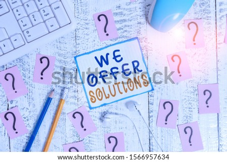 Writing note showing We Offer Solutions. Business photo showcasing Offering help assistance Experts advice strategies ideas Writing tools and scribbled paper on top of the wooden table. #1566957634