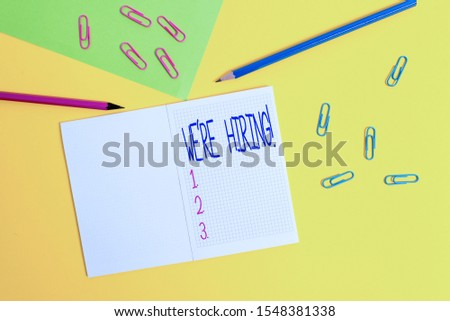 Writing note showing We Re Hiring. Business photo showcasing recently employ someone or pay him to do particular job Blank squared notebook pencils markers paper sheet colored background.