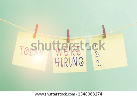 Writing note showing We Re Hiring. Business photo showcasing recently employ someone or pay him to do particular job Clothesline clothespin rectangle shaped paper reminder white wood desk.
