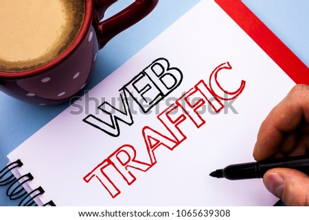 Writing note showing  Web Traffic. Business photo showcasing Internet Boost Visitors Audience Visits Customers Viewers written on Notebook Book Holding Pen on the plain background Coffee Cup. #1065639308