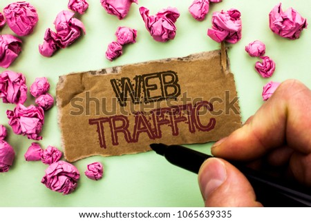 Writing note showing  Web Traffic. Business photo showcasing Internet Boost Visitors Audience Visits Customers Viewers written by Man Holding Marker on Tear Cardboard Piece plain background. #1065639335