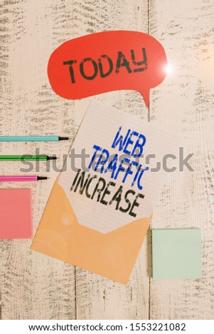 Writing note showing Web Traffic Increase. Business photo showcasing Expand Visitors to a Website a number of Visits Envelop speech bubble paper sheet ballpoints notepads wooden background.