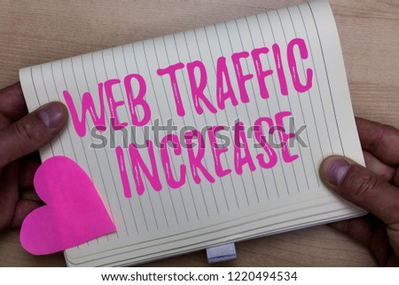Writing note showing Web Traffic Increase. Business photo showcasing Expand Visitors to a Websitea number of Visits Man holding notebook paper heart Romantic ideas Wooden background. #1220494534