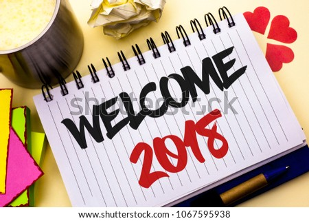 Writing note showing  Welcome 2018. Business photo showcasing Celebration New Celebrate Future Wishes Gratifying Wish written on Notebook Book on the plain background Cup Pen Hearts #1067595938