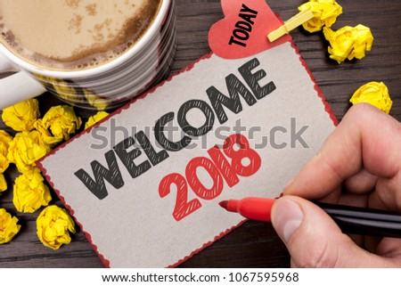 Writing note showing  Welcome 2018. Business photo showcasing Celebration New Celebrate Future Wishes Gratifying Wish written Man Holding Marker on Cardboard wooden background Today Coffee. #1067595968