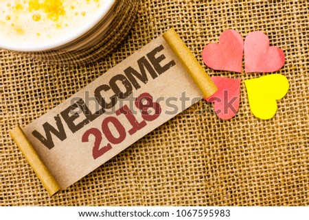 Writing note showing  Welcome 2018. Business photo showcasing Celebration New Celebrate Future Wishes Gratifying Wish written on sticky Note on the jute background Love Hearts next to it. #1067595983