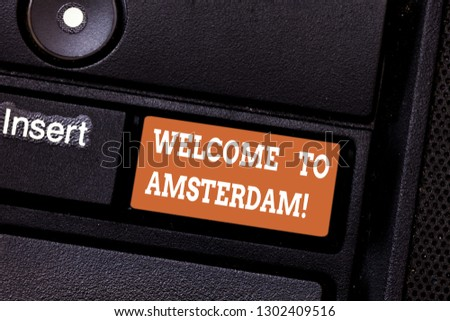 Writing note showing Welcome To Amsterdam. Business photo showcasing Greeting someone visits the capital city of Netherlands Keyboard key Intention to create computer message pressing keypad idea. #1302409516