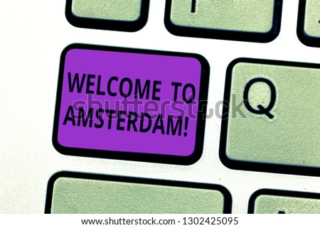 Writing note showing Welcome To Amsterdam. Business photo showcasing Greeting someone visits the capital city of Netherlands Keyboard key Intention to create computer message pressing keypad idea. #1302425095