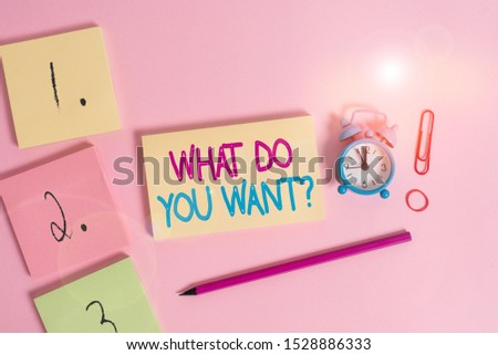 Writing note showing What Do You Want Question. Business photo showcasing Tell me your desires requests deanalysisds ambition Blank notepads marker rubber band alarm clock clip colored background.