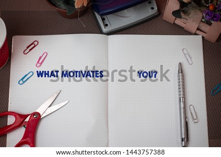 Writing note showing What Motivates Youquestion. Business photo showcasing know reasons why you want to wake up each morning Scissors and writing equipments plus math book above textured backdrop.