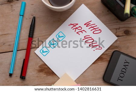 Writing note showing Who Are You question. Business photo showcasing asking demonstrating identity or demonstratingal information Wooden table stationary tablet coffee cup New project challenges.