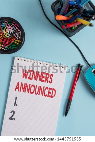 Writing note showing Winners Announced. Business photo showcasing Announcing who won the contest or any competition Notebook and stationary with mouse above pastel backdrop.