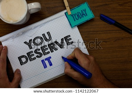 Writing note showing You Deserve It. Business photo showcasing Reward for something well done Deserve Recognition award Hand hold pen coffee cup blue pen paper clip stick on woody table. #1142122067