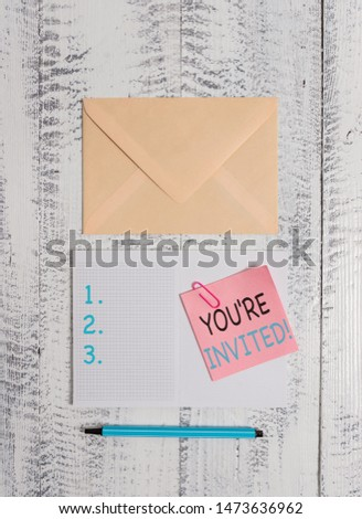 Writing note showing You Re Invited. Business photo showcasing make a polite friendly request to someone go somewhere Envelop squared notepad note clip marker old wooden vintage background. #1473636962