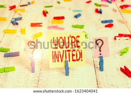 Writing note showing You Re Invited. Business photo showcasing make a polite friendly request to someone go somewhere Crumbling sheet with paper clips placed on the wooden table.