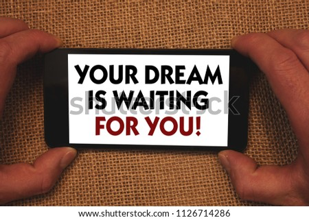Writing note showing  Your Dream Is Waiting For You. Business photo showcasing Goal Objective Intention Target Yearning Plan Man holding cell phone white screen message app wicker background. #1126714286