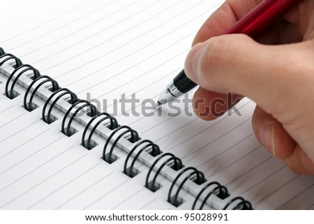 Writing notes or planning a schedule on blank spiral notebook for copy