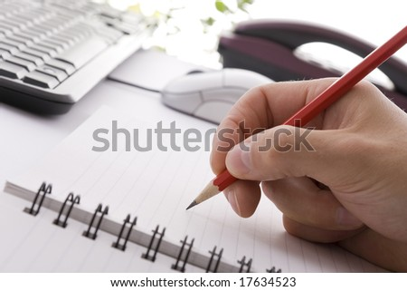Writing on a notepad with a pencil