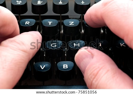 Writing on a typewriter. Fingers are visible