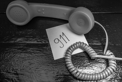 Writing 911 on memo post reminder.  sticky paper with text 911 and landline phone.