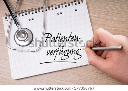 Writing pad and hand with pen writing the german words advance directive / advance directive
