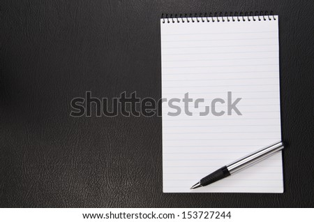 Writing pad and pen on a black leather texture