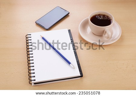 writing pad with pencil, smart phone and cup of coffee on desk
