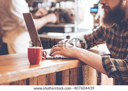 Writing post from cafe. Close-up part of young bearded man using his laptop while sitting at bar counter at cafe with barista at the background