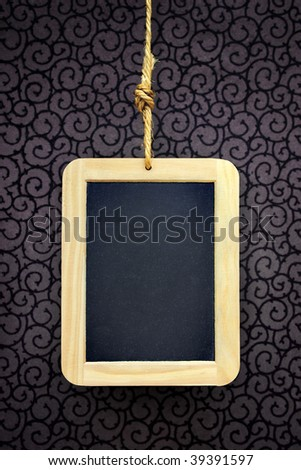 Writing slate hanged with a rope over a wallpaper with curly pattern