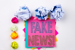 Writing text showing Fake News written on sticky note in office with screw paper balls. Business concept for Propaganda Newspaper Fake News on white isolated background.