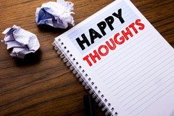 Writing text showing Happy Thoughts. Business concept for Happiness Thinking Good written on notebook notepad note paper on wooden background with folded paper meaning thinking for idea
