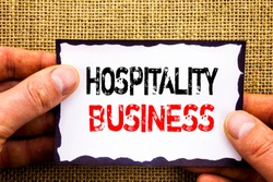 Writing text showing  Hospitality Business. Concept meaning Industry Business Tourism Advertisement written Sticky Note Paper Holding Hand with Finger.