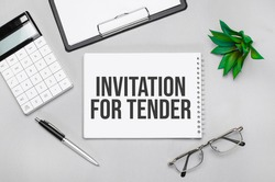 Writing text showing INVITATION FOR TENDER. Calculator,pen,plan,glasses and black folder on grey background