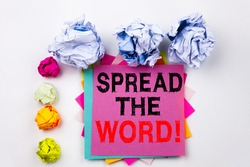 Writing text showing Spread The Word written on sticky note in office with screw paper balls. Business concept for Announcement Business Marketing Message on white isolated background.