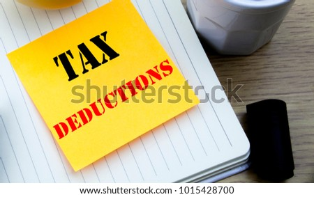 Writing text showing Tax Deductions. Business concept for Finance Incoming Tax Money Deduction written sticky note paper, Wooden background with copy space, Coffee and marker Stock photo ©