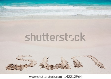 writing the text sun in the white caribbean sand with the sea or ocean behind it