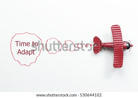 writing time to adapt red toy airplane with talk bubble on white background #530644102