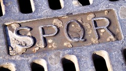 written SPQR on cast iron manhole in the sun, in a street in Rome