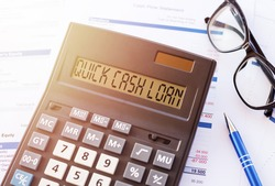 written text quick cash loan in calculator on office table with glasses and pen. Business and banking concept