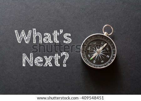 Written What's Next words on black background with compass