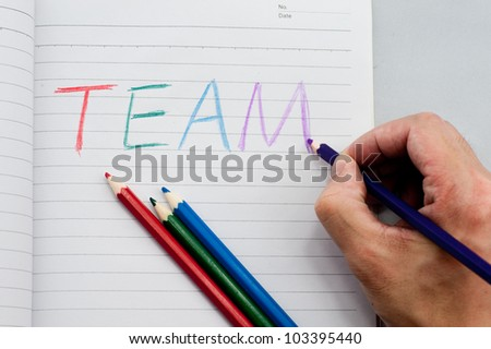 "written word ""team"" on the paper by colorful pencils"