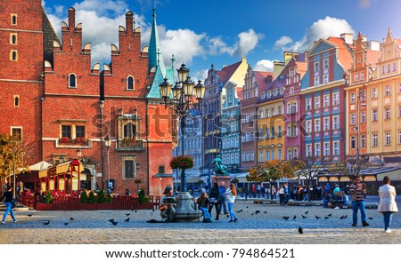 Wroclaw central market square with old colourful houses, street lamp and walking tourists people at evening sunset sunshine. #794864521
