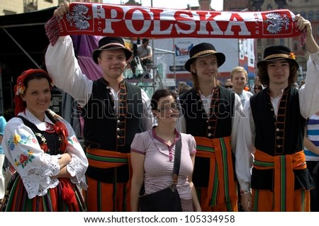 "WROCLAW, POLAND - JUNE 15:  Members of Folk Dance group ""Wroclaw"" visit Euro 2012 fanzone. Dancers take photo with football fan on June 15, 2012 in Wroclaw."